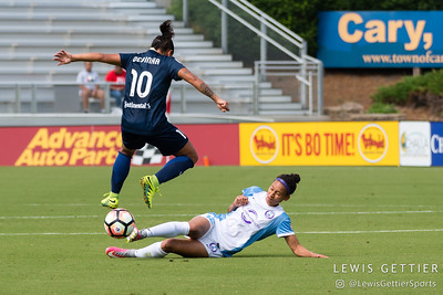Debinha (10) leaps over a tackle by Kristen Edmonds (12) during a match between the NC Courage and the Orlando Pride in Cary, NC in Week 3 of the 2017 NWSL season. Photo by Lewis Gettier.