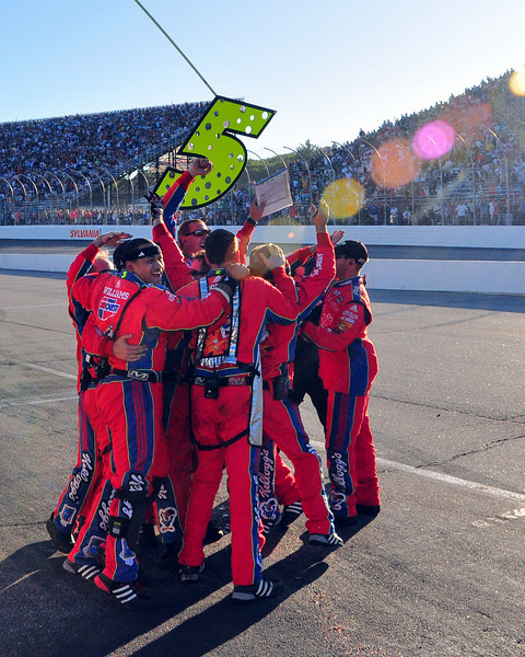 With the sun about to drop behind the grandstand, Mark Martin's pit crew reacts in jubilation, as a last lap wreck sealed his victory in the Sylvania 300, held at New Hampshire Motor Speedway on Sept. 20th, 2009