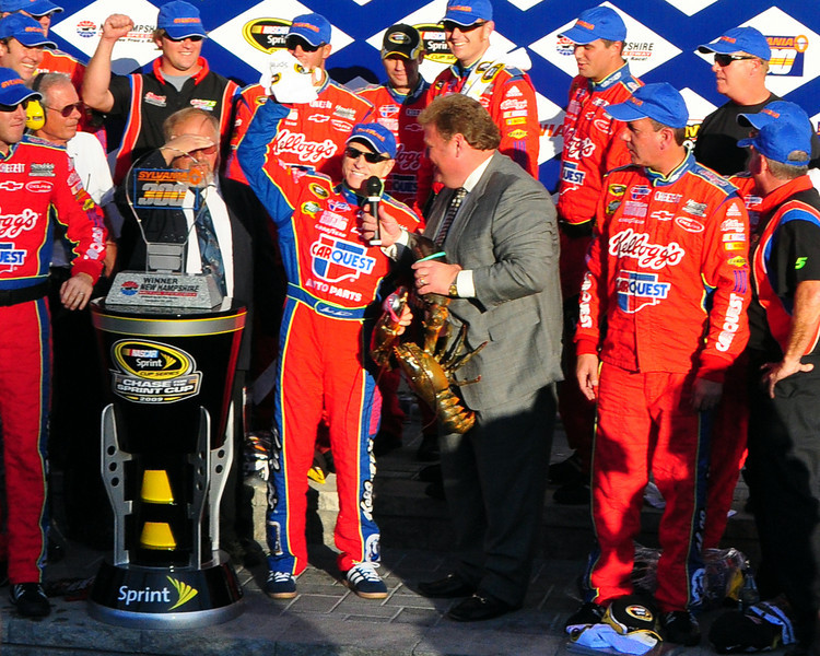 Mark Martin is presented the trophy for winning the Sylvania 300, by Jerry Gappens, Vice President & General Manager of New Hampshire Motor Speedway. In addition, Mr. Gappens is presented a large New Hampshire lobster. The victory also puts Mr. Martin at the top of the points in the Chase for the Sprint Cup Championship.