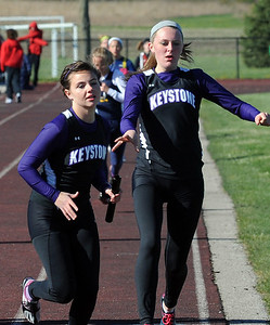 Keystone's Cate Shaw, front, takes handoff from Jillian Peters in the girls 4X800 relay at the Nelson Howe Invitational at Firelands on Apr. 5.  Steve Manheim