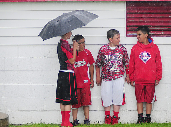 Neshannock fans take cover under the back of the dugout during a rain delay.