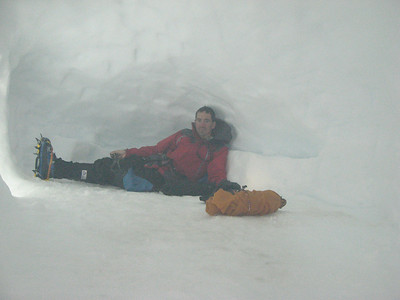 Trent lying in the kitchen area of the snow cave. To the left is the exit. Photo is taken from the foot of the sleeping area.