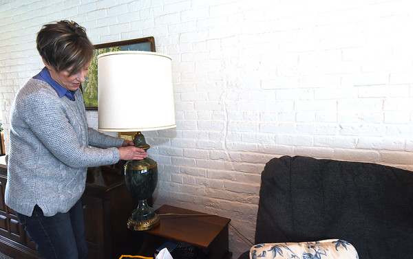 Anne Patterson Doyle moves a lamp that hides a large crack Patterson Doyle says was caused by a cannonball in her Civl War era home. Patterson Doyle grew up next door to the house that once served as a Civil War hosptal and command post. s an adult, she purchased the historic property.<br /> Globe   Laurie Sisk