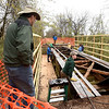 From the left: Dan Diehl, of the Joplin Trails Coalition, watches as JTC volunteers and students and staff of the Pittsburg State University Construction Department work to shore up a bridge on Ruby Jack Trail on Saturday.<br /> Globe | Laurie Sisk
