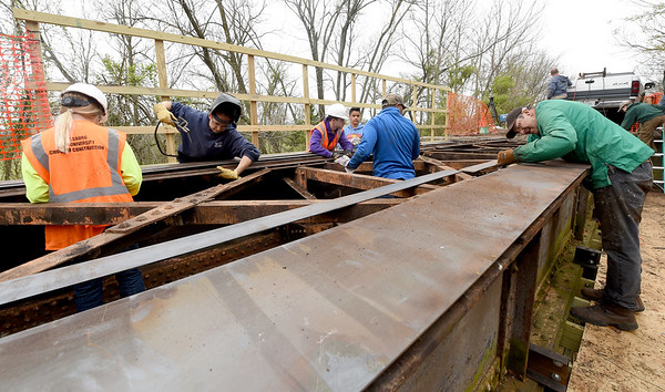 Joplin Trails Coalition volunteers and students and staff of the Pittsburg State University Construction Department work to shore up a bridge on Ruby Jack Trail on Saturday.<br /> Globe   Laurie Sisk