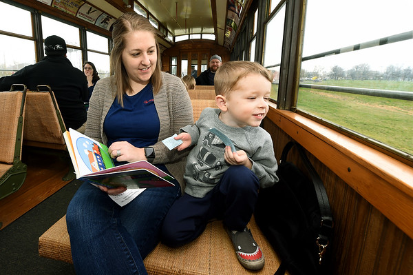 """Three-year-old Oliver Hawkins and his mother, Dani Hawkins, look for clues from the children's book, """"Peppa Pig and the Big Train,"""" during the Clickety Clack We're Reading Down the Track program on Saturday at the Webb City Farmers Market. Each third Saturday of the month, the program offers guests free rides and a new storytime courtesy of a partnership between the market, Friends of the Library, Webb City Parks and Recreation and the Southwest Missouri Railroad Association.<br /> Globe 