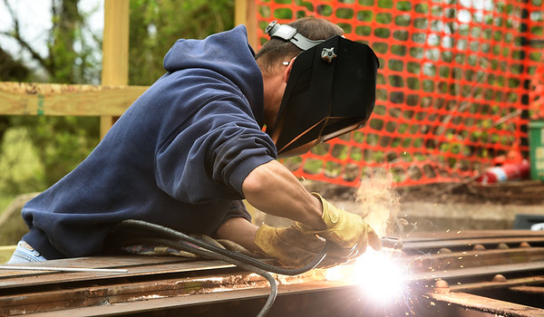 Mike Atkinson welds a portion of the a bridge as JTC volunteers and students and staff of the Pittsburg State University Construction Department work to shore up the bridge on Ruby Jack Trail on Saturday.<br /> Globe | Laurie Sisk