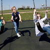 Six-year-old Ellie Ensz, center, provides the muscle as she pushes her sister, Mollie Ensz, 2 and Harlow Hamilton, 4, on the swings at King Jack Park in Webb City on Tuesday.<br /> Globe | Laurie Sisk