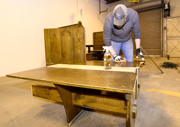 Volunteer Jared Aubert polishes a wooden booth table on Saturday in preparation for the opening of Empire Market.<br /> Globe | Laurie Sisk