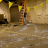 Volunteers string decorative lights on Saturday in preparation for the opening of Empire Market.<br /> Globe | Laurie Sisk