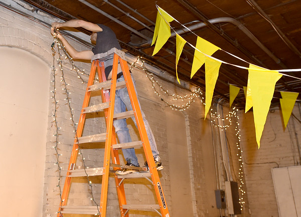Volunteer Tim Crawford strings decorative lights on Saturday in preparation for the opening of Empire Market.<br /> Globe | Laurie Sisk