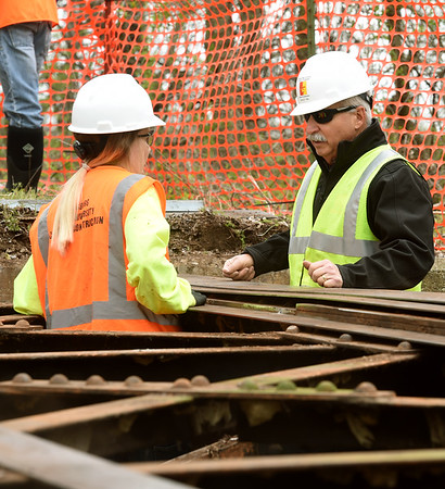 From the left: Pittsburg State University construction student Tiara Ewy consults with PSU Professor Randy Timi as JTC volunteers and members of their depsrtment work to shore up a bridge on Ruby Jack Trail on Saturday.<br /> Globe | Laurie Sisk