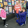 Cecil Floyd fourth grader Ariana Sampson, 9, gets her picture taken beside her artwork by her mother, Kimberly Sampson as her grandmother, Anna Voorhees looks on during the Joplin K-12 Art Show on Tuesday night at the Joplin High School Performing Arts Center. Student artists from each school in the Joplin R-VIII district were represented at the annual show.<br /> Globe | Laurie Sisk