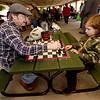 From the left: Nick Meyer and Maxwell Lynch, 7, enjoy a game of chess on Saturday at the Webb City Farmers Market.<br /> Globe | Laurie Sisk