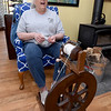 Deby Horner talks about the process of spinning alpaca wool into yarn as she works on her spinning wheel inside her Wyandotte home on Wednesday.<br /> Globe | Laurie Sisk