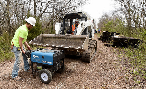 From the left: Aaron Elliott and Travis Solunder, of the Pittsburg State University Construction department,  transport a welder to a bridge on Ruby Jack Trail on Saturday as they work to shore up the bridge.<br /> Globe | Laurie Sisk