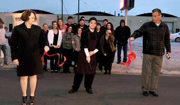 Flanked by Wilder's owners Marsha and Mike Pawlus, Wilder's Chef Jordan Burgess, center, cuts the ribbon for the newly restored neon at Wilder's on Saturday night.<br /> Globe | Laurie Sisk
