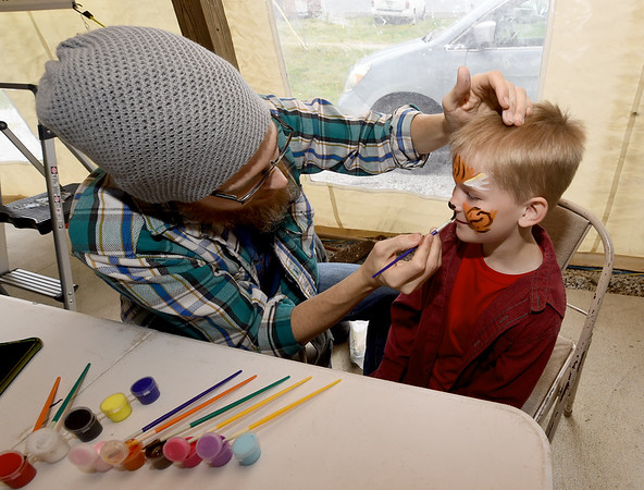 Six-year-old Dylan Morris gets his face painted as a tiger by Stephen Lynch on Saturday at the Webb City Farmers Market.<br /> Globe | Laurie Sisk