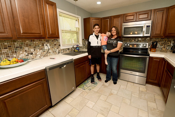 Nicole Velasco, right, stands in her remodeled Neosho kitchen with her son Matthew Velasco, 14 and daughter Chloe Alexander, 4 on Saturday. Velasco's home suffered extensive damage in last year's flooding.<br /> Globe | Laurie Sisk