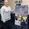 Joplin Go Red for Women Chair Jana Smith stands near a poster for her organization in her Carthage home on Thursday.<br /> Globe | Laurie Sisk