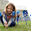 Five-year-old Harlow Duncan smiles as she plants one of 229 pinwheels on Saturday at the JPD. The 229 pinwheels displayed represent the number of cases of child abuse the department investigated in 2017.<br /> Globe | Laurie Sisk