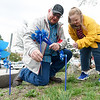 Joplin Police Officer Ben Cooper and his daughter, Ashley Cooper, 11, help plant pinwheels on Saturday at the JPD. The 229 pinwheels displayed represent the number of cases of child abuse the department investigated in 2017.<br /> Globe | Laurie Sisk