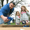From the left: Joplin Police Department Sgt. Andy Blair assists 3-year-old Haedyn Duncan and her sister, 5-year-old Harlow Duncan as they prepare to plant 229 pinwheels on Saturday at the JPD. The 229 pinwheels displayed represent the number of cases of child abuse the department investigated in 2017.<br /> Globe | Laurie Sisk