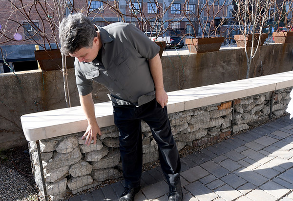 Developer Jeff Neal points out the use of what other builders might deem demolition material, but materials Neal has repurposed into the design of an outdoor courtyard.<br /> Globe | Laurie Sisk