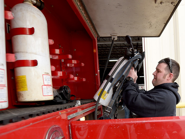 Goodman Area Fire Protection District volunteer Derek Parsons loads a tank onto a truck on Thursday at the department's leased space in Goodman.<br /> Globe   Laurie Sisk