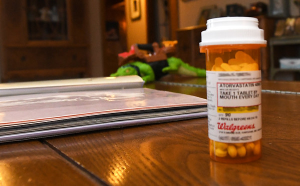 A bottle of cholesterol-lowering medication sits beside a family photo album in Jana Smith's Carthage home on Thursday.<br /> Globe | Laurie SIsk