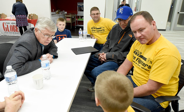 Joplin City Council candidate Doug Lawson, left, listens to firefighters and their families about their concerns during a meet and greet on Thursday night at the Joplin Public Library.<br /> Globe   Laurie Sisk