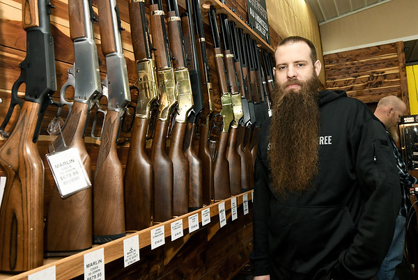 Liberty Tree owner Eli Bruton stands by a rack of rifles at his Carthage store on Thursday.<br /> Globe   Laurie Sisk