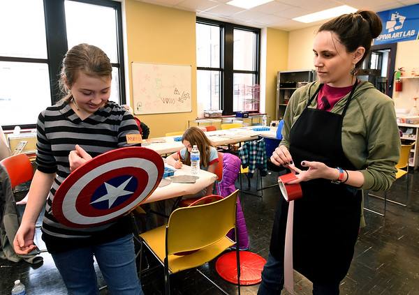 From the left: Abby Davis, 13, tries on her Captain America shield during Superhero Adventure Recycling Camp as teacher Sarah Serio looks on Tuesday at the Spiva Center for the Arts. The shields were made from recycled pizza pans and duct tape.<br /> Globe | Laurie SIsk