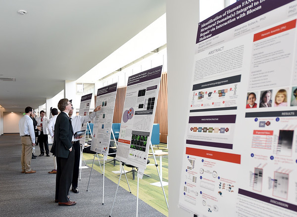 Student doctors and medical professionals check put some of the 35 research projects on display during the  the 26th Annual Kansas City University Research Symposium on Wednesday at KCU. <br /> Globe   Laurie SIsk