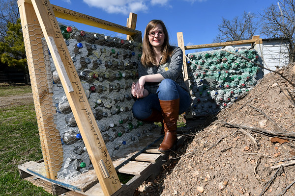 Missouri Southern physics major and U.S. Army veteran Kaitlyn Gonzalez poses near the walls she created from soda bottles filled with sand, right, and dirt, left on her grandparents farm in Granby on Wednesday. Gonzalez tested the walls by firing various calibers of ammunition, with none piercing the walls more than halfway.<br /> Globe | Laurie Sisk
