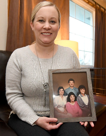 Jana Smith holds a family photo in her Carthage home on Thursday. Pictured in the photo are front row, from the left: Smith's aunt, Robin Pessley, Smith's mother, Rhonda Fisher, who died from a heart attack when Smith was 16, Smith's aunt, Renee Sidenstricker, who endured a quadruple by-pass before she died and Smith's uncle, Rusty Sidenstricker.<br /> Globe   Laurie Sisk
