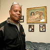 Eddie Thomas stands near a family portrait in his East Joplin home.<br /> Globe | Laurie SIsk