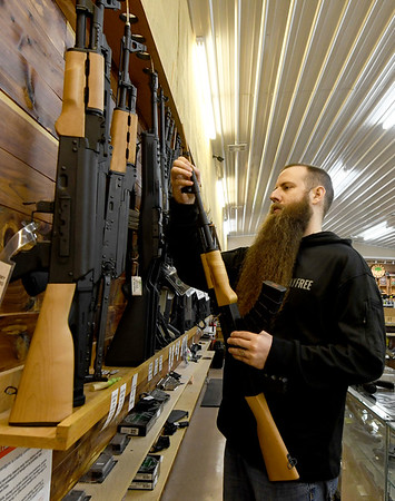 Liberty Tree owner Eli Bruton holds a WASR-10 semiautomatic rifle at his Carthage store on Thursday.<br /> Globe | Laurie Sisk
