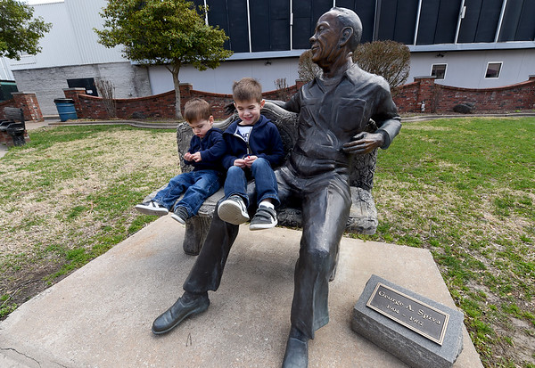 From the left: Brothers Hawthorne Dickerson, 22 mths and Rafferty Dickerson, 4, share a visit with a statue of George Spiva on Saturday at Spiva Park.<br /> Globe | Laurie Sisk