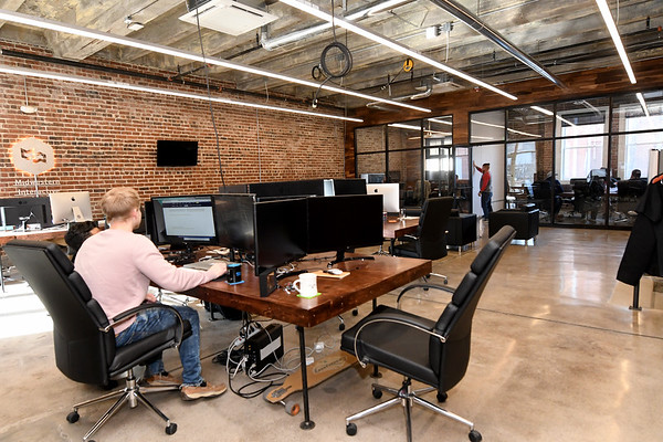Software developers from Midwestern Interactive work inside the recently renovated Hurlburt Building at 212 South Joplin St. on Thursday. The building once served as Hurlbut Mortuary and was later home to the Salvation Army.<br /> Globe | Laurie Sisk