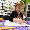 Three-year-old Addelyn Springer, of Webb City, gets in the Easter spirit at the coloring station at Natural Grocers during the store's Eggcellent Adventure on Friday. The event featured an Easter Egg Hunt, coloring station, prizes and more.<br /> Gobe | Laurie Sisk
