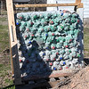 Missouri Southern physics major and U.S. Army veteran Kaitlyn Gonzalez created this wall from soda bottles filled with sand on her grandparents farm in Granby on Wednesday. Gonzalez tested the walls by firing various calibers of ammunition, with none piercing the walls more than halfway.<br /> Globe | Laurie Sisk