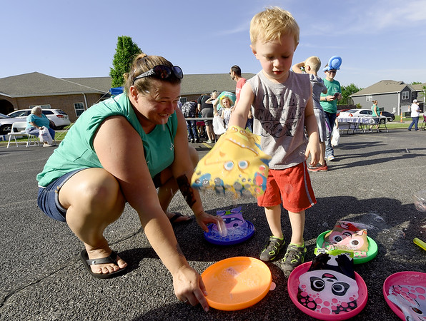 Three-year-old Grayson Heckmaster, of Baxter Springs, explores the wonderful world of bubbles as Will's Place caseworker Tonya Landrum assists during The Sixth Annual  Will's Place Children's Block Party on Thursday at Will's Place. The event, which featured food, music and games, aimed to increase awareness about children's mental health issues.<br /> Globe | Laurie Sisk