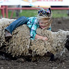 Six-year-old Carolina Land, of Wyandotte, holds on to her sheep during the mutton busting competition at Rodeo Miami on Saturday at the Miami Fairgrounds.<br /> Globe | Laurie Sisk