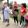Third grade teacher LaChrista Earll, center, gathers her students from Commerce's Alexander Elementary for their return bus ride to Commerce on Tuesday at Cunningham Park. About 120 students from Alexander were rewarded for their performance on state standardized testing with a day of rollerskating and picnicing at the park.<br /> Globe | Laurie Sisk