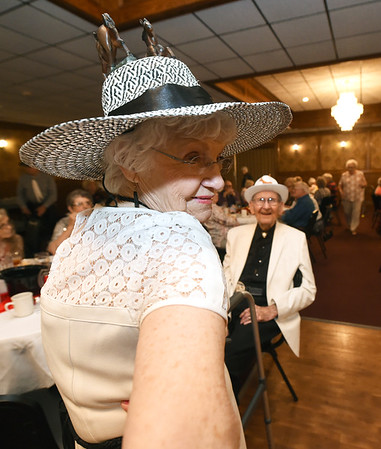 Joan McMullen Thompson shows of her Kentucky Derby-themed bonnet as her husband Tommy Thompson looks on during the Area Agency on Agency's Senior Prom on Wednesday at The Butcher's Block. The couple met at the dance five years ago and have been married for four years.<br /> Globe | Laurie Sisk
