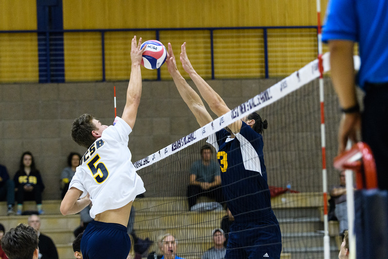Freshman Keenan Sanders jousts with the UC Irvine middle blocker, maintaining control of the ball and winning the point.