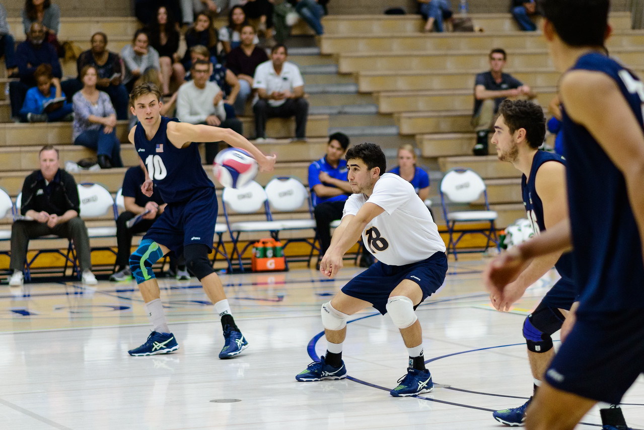 Parker Boehle receives a powerful jump serve from the Captain of the Lewis team.
