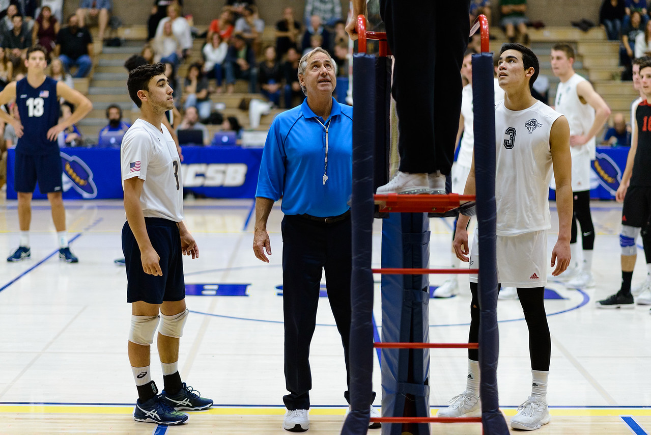 Parker Boehle and the Lewis floor captain listen as the down-ref and up-ref discuss the ruling of a play.