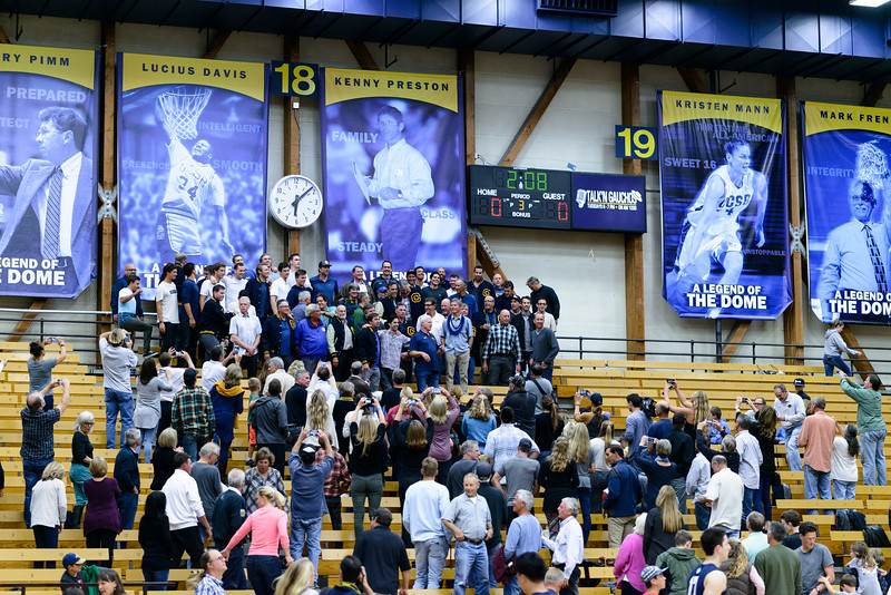 Coach Kenny Preston joins members of the UCSB volleyball community, both past and present, for a photo with his newly unveiled banner.